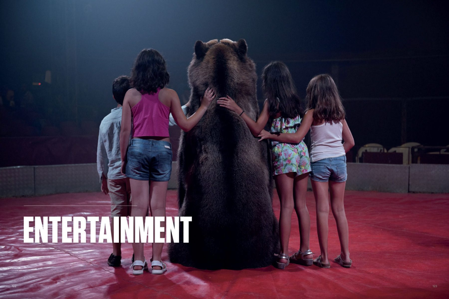 Tima the brown bear of the Gran Circo Holiday circus poses for a photo with children. Spain. Aitor Garmendia