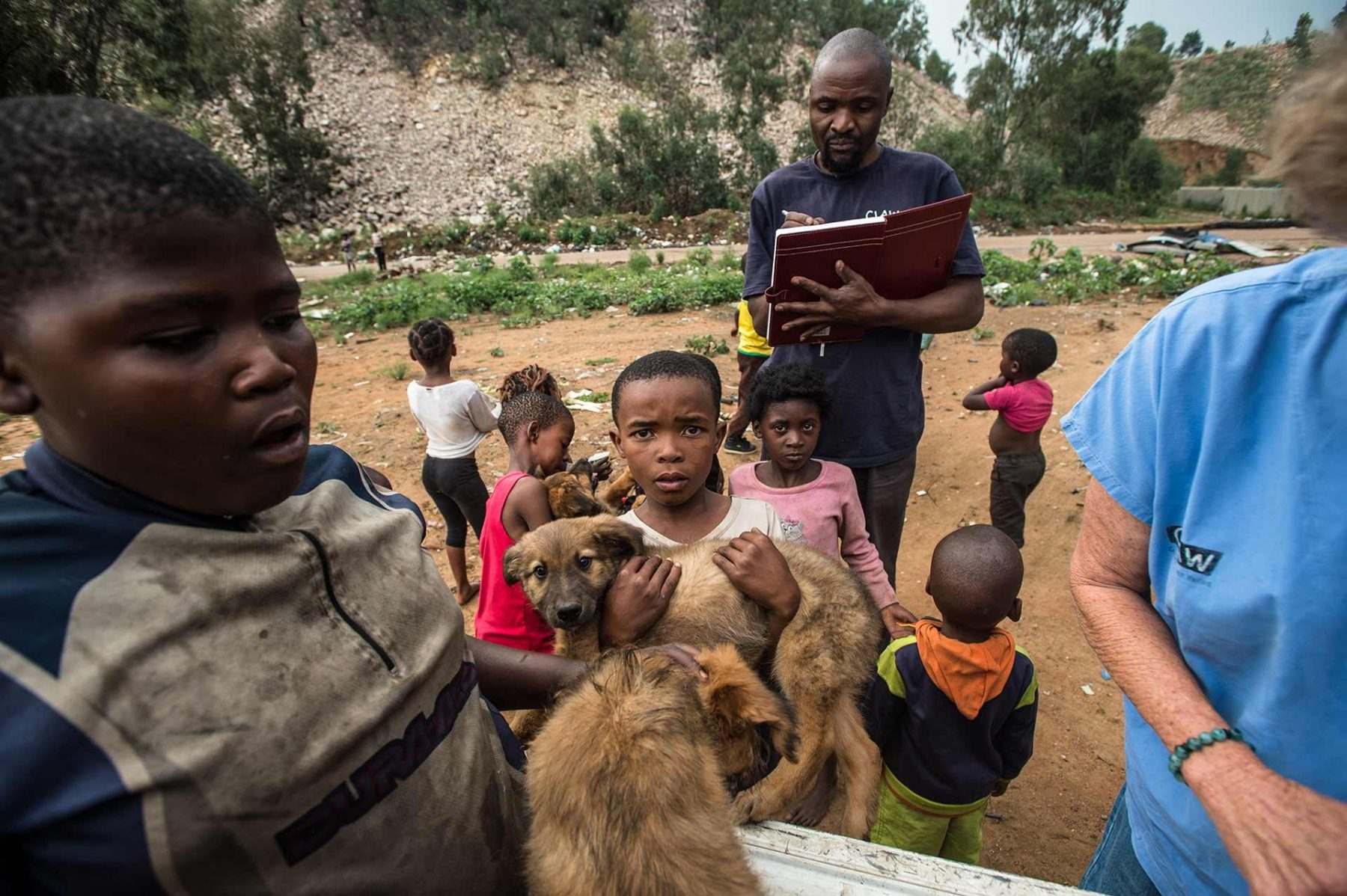 Children bringing their animals to the C.L.A.W. vehicle for health checks at the Randfontein municipal dumping site in Johannesburg. South Africa.