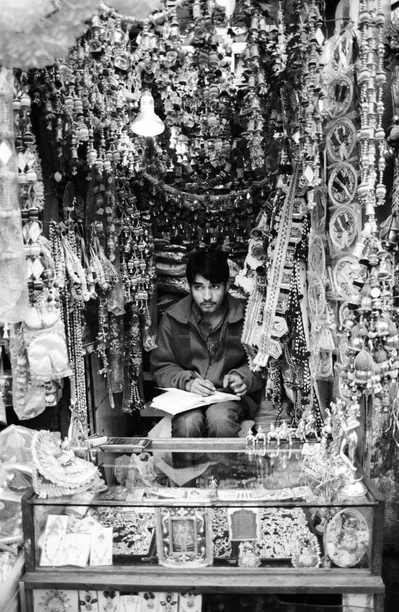 Man in a market stall. India.