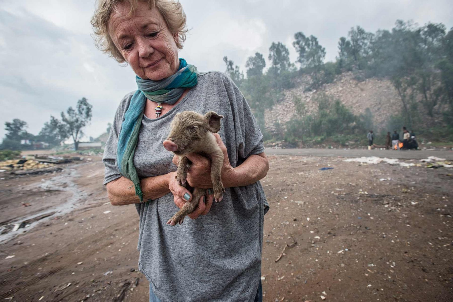 Cora Bailey, founder of Community Led Animal Welfare (CLAW), rescuing a piglet at the Randfontein Dump in Johanessburg. South Africa, 2016